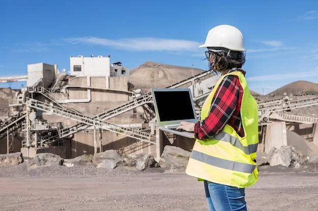 Zijaanzicht van vrouwelijke ingenieur in veiligheidshelm en gilet die op laptop met zwart scherm werkt tijdens een bezoek aan de bouwplaats van de onvoltooide industriële faciliteit