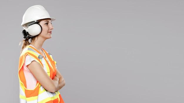 Zijaanzicht van vrouwelijke ingenieur met exemplaarruimte en helm