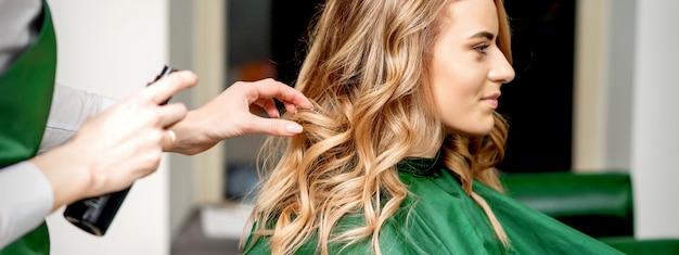 Zijaanzicht van vrouwelijke kapper die haarlak gebruikt die het vrouwelijke haar van klanten in een kapsalon bevestigt