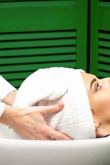 Zijaanzicht van vrouwelijke kapper droogt het haar van de vrouwelijke klanten met een handdoek in de gootsteen bij een kapsalon