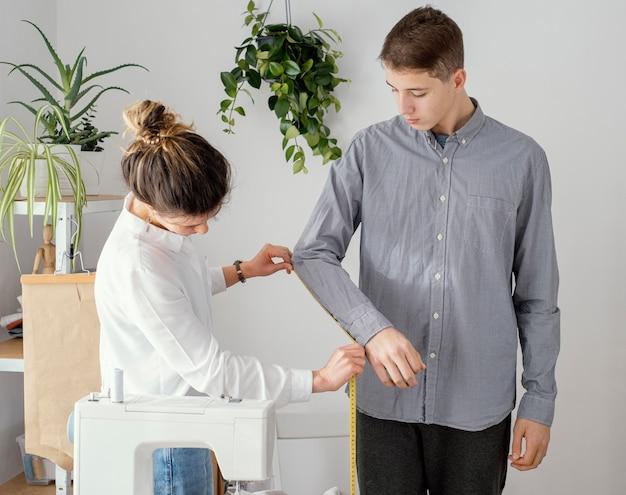 Zijaanzicht van vrouwelijke kleermaker die het overhemd van mannelijke cliënten meten