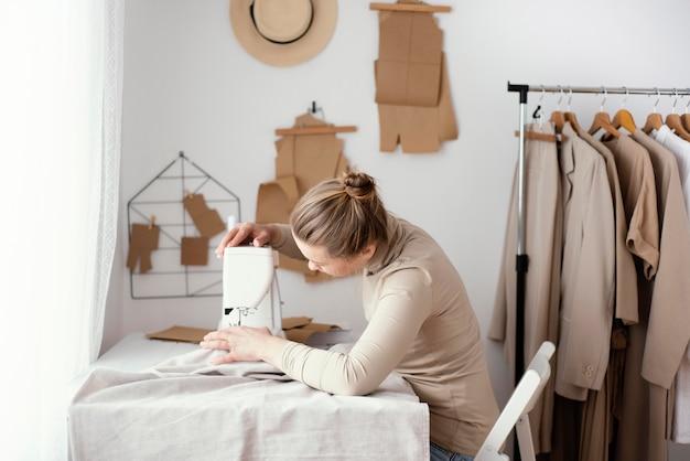 Zijaanzicht van vrouwelijke kleermaker die in de studio met naaimachine werkt