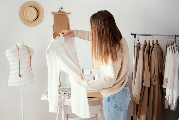 Zijaanzicht van vrouwelijke kleermaker die kledingstukken controleert