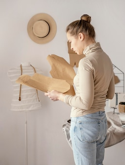 Zijaanzicht van vrouwelijke kleermaker patronen in de studio controleren