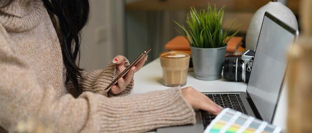 Zijaanzicht van vrouwelijke ontwerper die met laptop en smartphone aan witte lijst in bureauruimte werkt