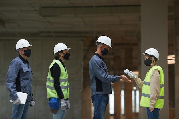 Zijaanzicht van vrouwelijke supervisor die de temperatuur van werknemers meet met contactloze thermometer wijzend op handen,