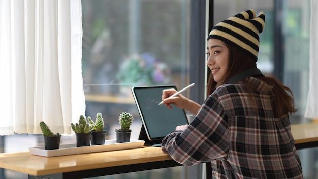 Zijaanzicht van vrouwelijke tiener met behulp van mock-up digitale tablet op balk in coffeeshop