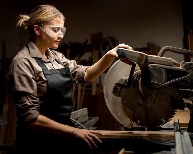 Zijaanzicht van vrouwelijke timmerman met gereedschap
