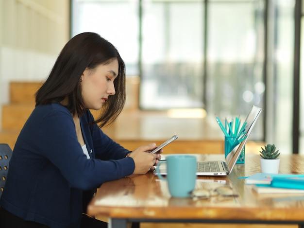 Zijaanzicht van vrouwelijke universiteitsstudent die smartphone gebruikt terwijl huiswerk in co werkruimte