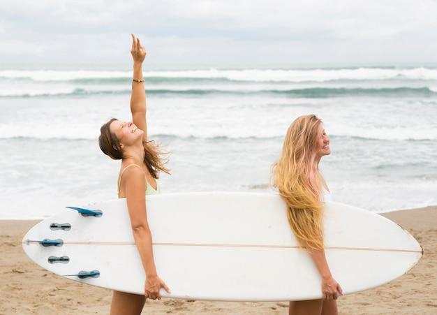 Zijaanzicht van vrouwelijke vrienden die een surfplank houden op het strand