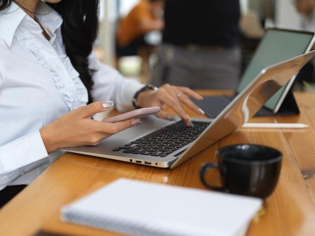Zijaanzicht van vrouwelijke werknemer die met laptop en smartphone werkt op houten tafel in kantoorruimte