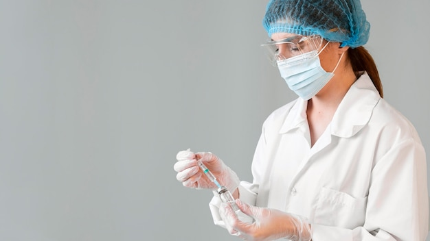 Zijaanzicht van vrouwelijke wetenschapper met veiligheidsbril en medische masker met spuit