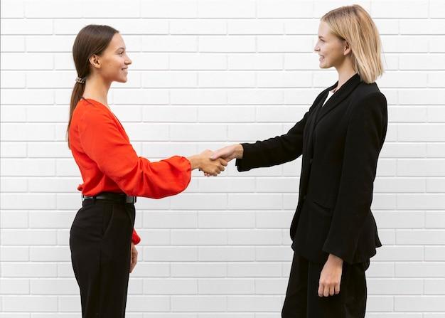 Zijaanzicht van vrouwen die elkaar groeten
