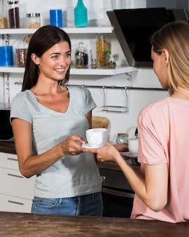 Zijaanzicht van vrouwen die koffie thuis delen