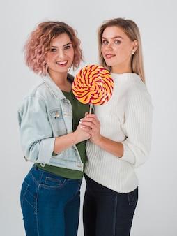 Zijaanzicht van vrouwen die met lolly voor valentijnskaarten stellen