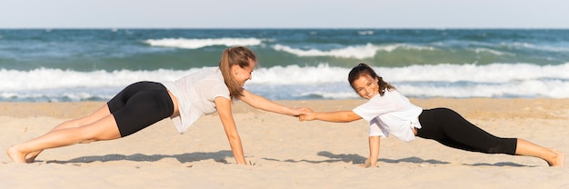 Zijaanzicht van vrouwen die push-ups op het strand doen