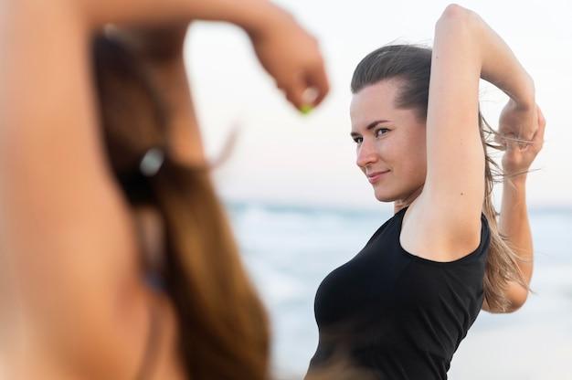 Zijaanzicht van vrouwen die zich uitstrekken op het strand voordat ze gaan trainen