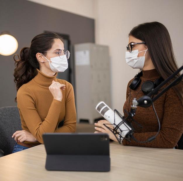 Zijaanzicht van vrouwen met medische maskers die een radioshow doen