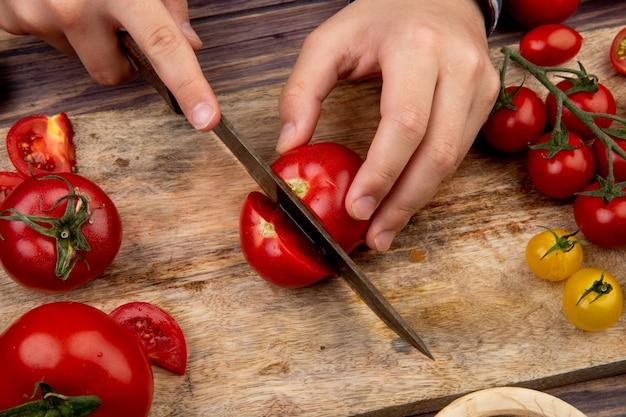 Zijaanzicht van vrouwenhanden die tomaat op scherpe raad met mes op houten oppervlakte snijden