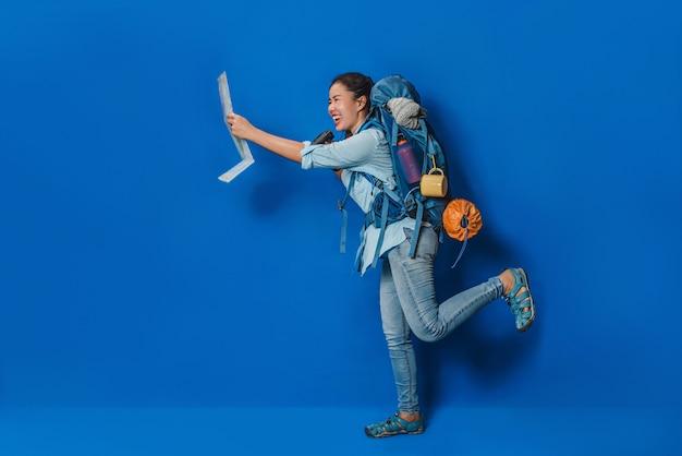 Zijaanzicht van vrouwenreiziger met kofferrugzak