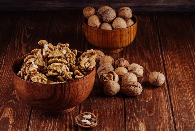 Zijaanzicht van walnoten in een houten kom op donkere rustieke achtergrond