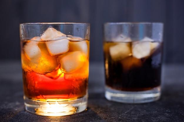 Zijaanzicht van whisky of rum met cola en ijs in glazen op een donkere achtergrond