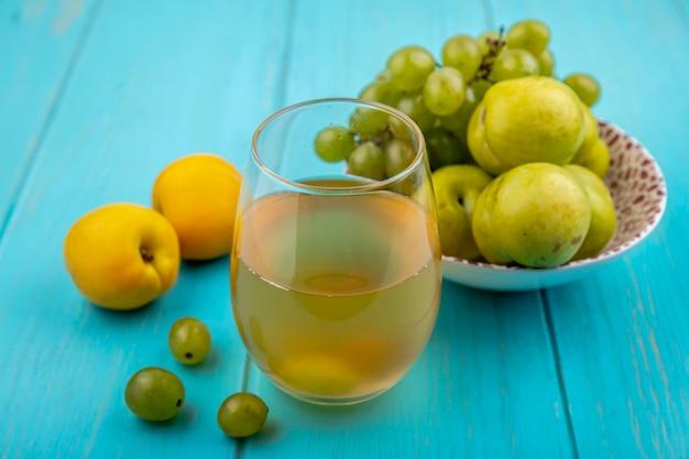 Zijaanzicht van wit druivensap in glas en fruit als druif en groene plukken in kom met nectacots en druiven bessen op blauwe achtergrond