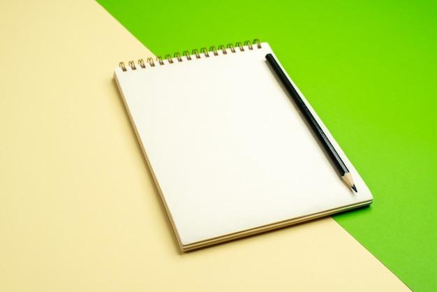 Zijaanzicht van wit notitieboekje met pen op witte en gele achtergrond