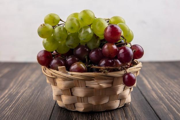 Zijaanzicht van witte en rode druiven in mand op houten oppervlak en witte achtergrond