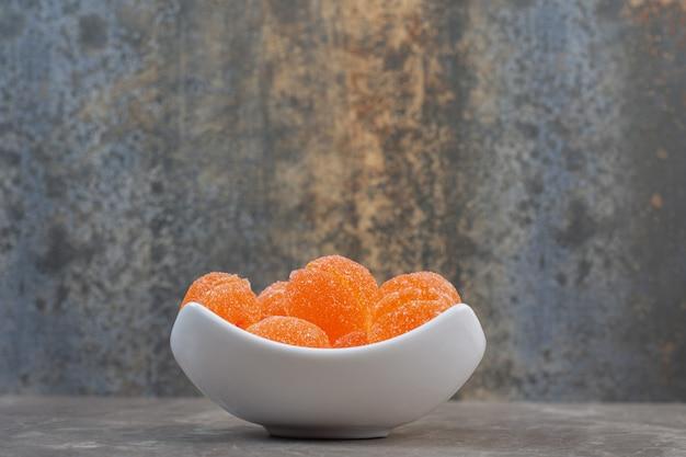 Zijaanzicht van witte keramische kom vol met oranje lekkere snoepjes.