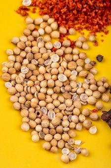 Zijaanzicht van witte peper met gedroogde chili peper vlokken op gele achtergrond