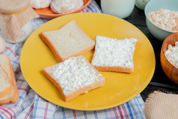 Zijaanzicht van witte sneetjes brood besmeurd met kwark in plaat met peperkoek havervlokken room rond op geruite doek en houten oppervlak