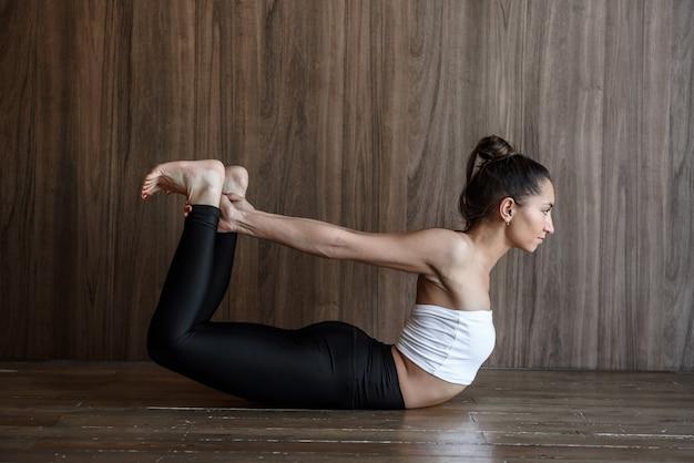 Zijaanzicht van yoga vrouw beoefenen van rekoefening op de vloer terug