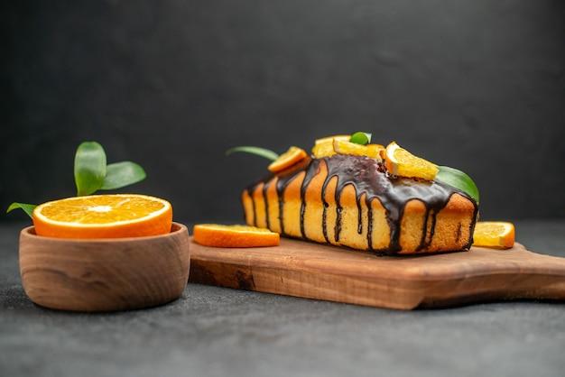 Zijaanzicht van zachte taarten op snijplank en gesneden sinaasappels met bladeren op donkere tafel