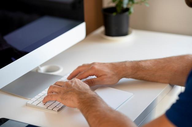 Zijaanzicht van zaken man handen met behulp van computer zittend aan een bureau in kantoor aan huis
