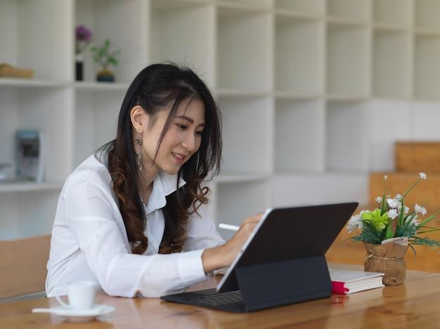 Zijaanzicht van zakenvrouw bezig met haar project met tablet in de comfortabele kantoorruimte