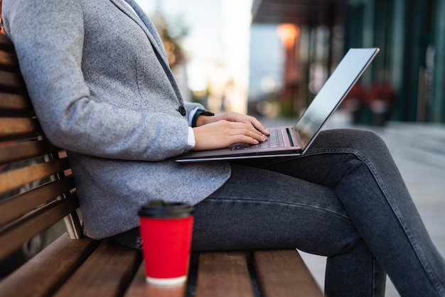 Zijaanzicht van zakenvrouw die op laptop buitenshuis met kopje koffie werkt