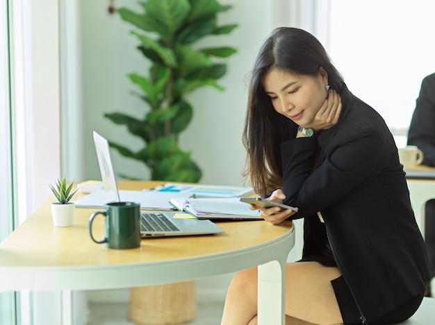 Zijaanzicht van zakenvrouw ontspannen met smartphone zittend in kantoorruimte