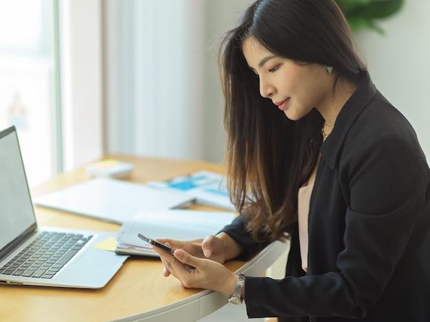 Zijaanzicht van zakenvrouw ontspannen van het werk met smartphone op werkplek
