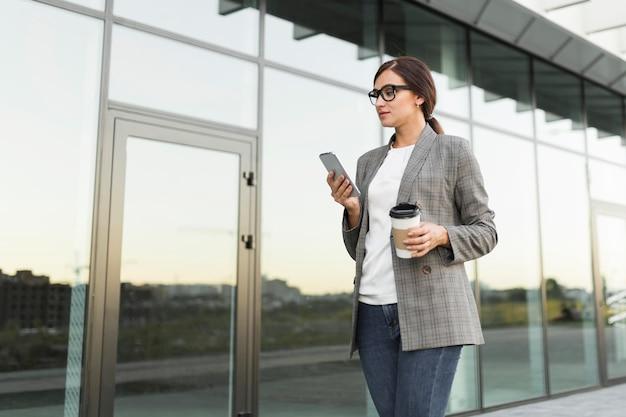 Zijaanzicht van zakenvrouw smartphone buitenshuis controleren terwijl het drinken van koffie