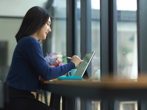 Zijaanzicht van zakenvrouw werken met digitale tablet op balk in café