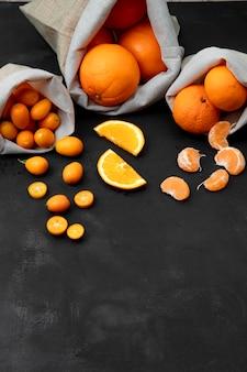 Zijaanzicht van zakken vol citrusvruchten als oranje mandarijn kumquat op zwarte ondergrond
