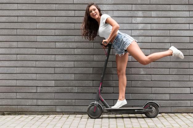 Zijaanzicht van zeer gelukkige vrouw die zich voordeed op elektrische scooter