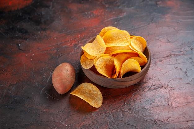 Zijaanzicht van zelfgemaakte heerlijke knapperige chips in een kleine bruine kom aan de linkerkant van een donkere achtergrond