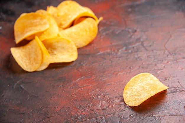 Zijaanzicht van zelfgemaakte heerlijke knapperige chips opgesteld op een donkere achtergrond rechtenvrije stockafbeeldingen