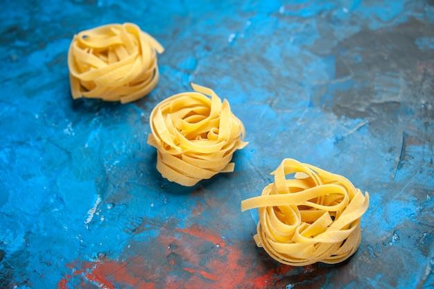 Zijaanzicht van zelfgemaakte verse tagliatelle pasta's opgesteld in een rij op blauwe achtergrond