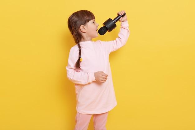 Zijaanzicht van zingend meisje dat bleekroze kledij draagt en vlechtjeskapsel, de microfoon van de kindholding heeft en tegen gele muur presteert.
