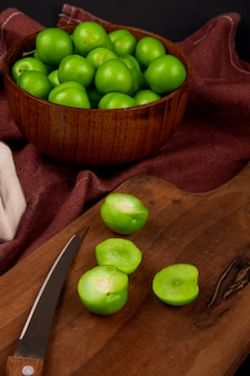 Zijaanzicht van zure groene pruimen in een houten kom en gesneden groene pruimen met een keukenmes op een houten bord op donkerrode stoffen tafel