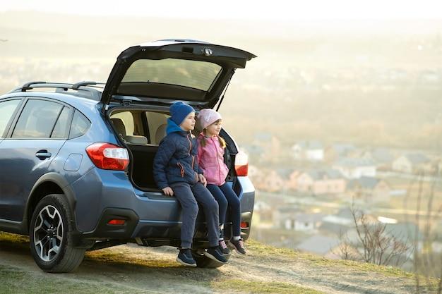 Zijaanzicht van zus en broer zitten in de kofferbak en kijken naar de natuur