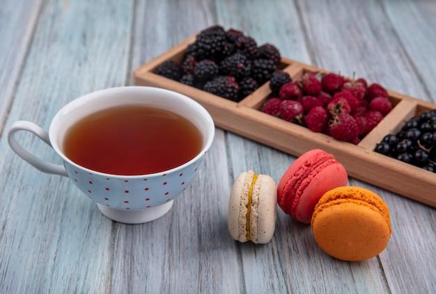 Zijaanzicht van zwarte bessen met frambozen en bramen op een stand met een kopje thee en gekleurde macarons op een grijze ondergrond